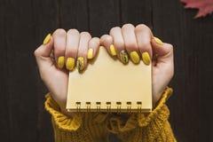 Gelber Notizblock in den weiblichen Händen Maniküre mit einem Muster Abschluss-u stockbilder