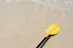 Gelber Paddelkajak auf dem Strand Stockbilder