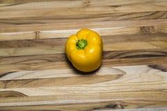 Gelber Pfeffer auf einem Teakholzschneidebrett Lizenzfreie Stockbilder