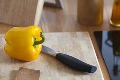 Gelber Pfeffer liegt mit einem Küchen-Messer auf einem Schneidebrett Stockfotos