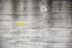 Gelber Pfeil auf Zementwand Stockfoto