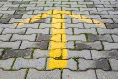 Gelber Pfeil gemalt auf grauer Pflasterung, StraßenWegweiser Stockfotos