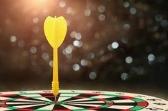gelber Pfeil mit unscharfem Überhintergrund und Ziel von dartboar Lizenzfreie Stockbilder
