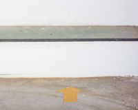 Gelber Pfeilaufkleber auf dem Boden mit Kopienraum Lizenzfreie Stockfotografie