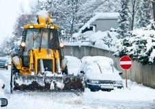 Gelber Planierraupen-Schnee, der Straße pflügt Stockfotografie