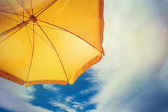 Gelber Regenschirm gegen blauen Himmel mit Wolken lizenzfreie stockfotografie