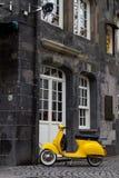 Gelber Retrostilroller unbeaufsichtigt in Essen Stockbilder