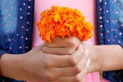 Gelber Ringelblumenblumen-Blumenstraußgriff durch Mädchen auf ihren Händen lizenzfreies stockbild