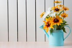 Gelber Rudbeckia, coneflowers, schwarz-musterte-susans, Blumen und andere sumer Blumen in einer blauen Gießkanne stockfoto