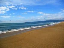 Gelber sandiger Strand und blaues Meer lizenzfreie stockfotos