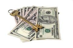 Gelber Schlüssel auf Dollarscheinen Stockbilder