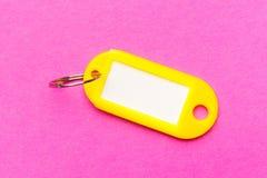 Gelber Schlüsselanhänger auf purpurrote Pappstrukturiertem Hintergrund Das Konzept des Mietens, verkaufend schablone Tendenzfarbe lizenzfreies stockbild