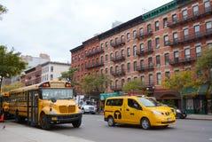 Gelber Schulbus und NYC-Taxi Lizenzfreie Stockfotos