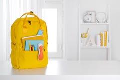 Gelber Schulrucksack auf Tabelle über Kinderrauminnenraum lizenzfreie stockfotografie
