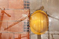 Gelber Schutzhelm der Bauarbeiter, der an der Betonmauer hängt Stockfotos