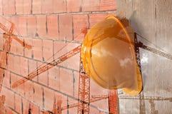 Gelber Schutzhelm der Bauarbeiter, der an der Betonmauer hängt Stockbild