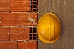 gelber Schutzhelm, der an der Betonmauer hängt Stockfotos