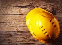 Gelber Schutzhelm-Gang auf Holztisch Lizenzfreies Stockfoto