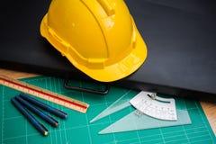 Gelber Schutzhelm-Hut und Ziehwerkzeuge Lizenzfreie Stockfotografie