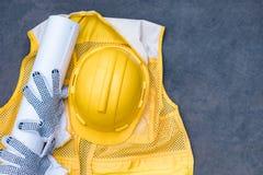 Gelber Schutzhelm mit Handschuh, Plan auf Weste auf Boden stockbilder