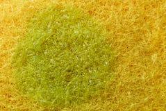Gelber Schwamm der Beschaffenheit und grünes Abwaschreinigungsmittel Lizenzfreies Stockbild