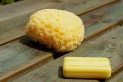 Gelber Schwamm und Seife auf hölzernen Panels Stockfotografie
