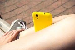 Gelber Smartphone auf den Beinen des Mädchens Stockbilder
