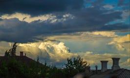 gelber Sonnenuntergang mit blauen Wolken über Dächern Lizenzfreies Stockbild