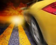 Gelber Sportwagen, der zum Sonnenuntergang antreibt Lizenzfreies Stockfoto