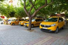 Gelber Stadttaxistand im Schatten von Bäumen lizenzfreie stockbilder