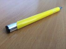 Gelber Stift auf Schreibtisch Stockbild