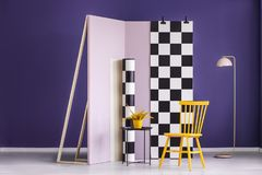 Gelber Stuhl und Anlage gegen Pastellrosawand mit kariertem f Stockfotos