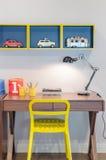 Gelber Stuhl und hölzerner Schreibtisch mit moderner schwarzer Lampe Lizenzfreie Stockfotografie