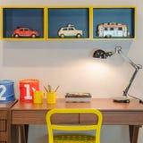Gelber Stuhl und hölzerner Schreibtisch mit moderner schwarzer Lampe Lizenzfreie Stockbilder