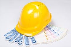 Gelber Sturzhelm, Arbeitshandschuhe und bunte Palette über Weiß Stockfoto