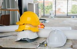 Gelber Sturzhelm auf oberstem weißem Sturzhelm, wenn Standort konstruiert wird lizenzfreies stockfoto