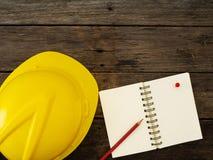 Gelber Sturzhelm und Bleistift auf Draufsicht des Notizbuches stockbilder