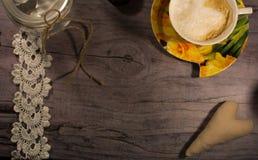 Gelber Tasse Kaffee auf der grauen Tabelle romantischer Hintergrund Lizenzfreie Stockfotos