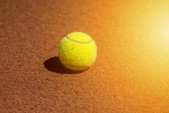 Gelber Tennisball auf einem Sandplatz lizenzfreies stockbild