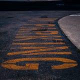 Gelber Text des Parkverbots auf dem schwarzen Asphalt stockbild