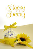 Gelber Themakleiner kuchen und -sonnenblume mit glücklichem Sonntag Lizenzfreie Stockbilder