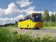 Gelber touristischer Bus auf Datenbahn und landwirtschaftlicher Landschaft Stockbild
