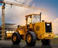 Gelber Traktor auf der Straße Stockfotos