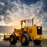 Gelber Traktor auf der Straße Lizenzfreie Stockbilder