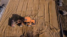 Gelber Traktor repariert die Straßenvogelperspektive lizenzfreies stockbild