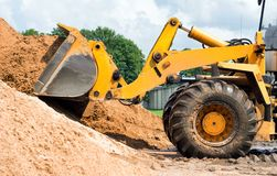 Gelber Traktorlader hebt einen Eimer Erde auf, mechanisch, Schöpflöffel mit Erde stockfoto