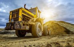 Gelber Traktorlader hebt einen Eimer von Erde auf, mechanisch, von Schöpflöffel mit Erde und von Sonne lizenzfreie stockbilder