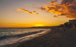 Gelber und orange Sonnenuntergang auf Strand in Nizza Stockfotografie