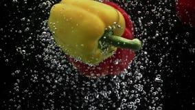 Gelber und roter grüner Pfeffer spritzt in Wasser auf schwarzem Hintergrund stock abbildung