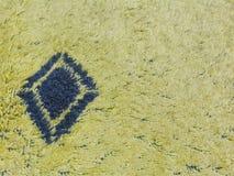 Gelber Unschärfehintergrund mit blauer Raute Stockfotografie